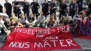 "Anti-G8 protestors sit near a banner which reads, ""Insecurity Leads to Fear. To Better Control Us"""