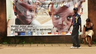 A security guard walks in front of a posters for the forthcoming presidential election
