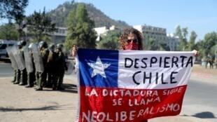 «Réveille-toi, Chili, la dictature continue, elle s'appelle néo-libéralisme», peut-on lire sur cette pancarte à Santiago du Chili le 27 décembre 2019.