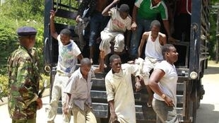Muslim youths, who were detained by police from Sunday's raid at the Masjid Musa mosque, disembark from a vehicle as they arrive at a court in Shanzu, near Monbasa, 3 February 2014.