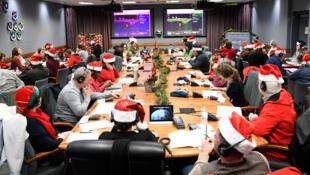 Des volontaires travaillant Centre d'opération Tracks Santa de la NORAD à Colorado Springs le 24 décembre 2018. Ils travaillent à suivre le chemin du Père Noël pendant toute sa tournée.