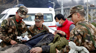Paramilitary police officers carry an injured victim following an explosion at a chemical industrial park in Yanchang, Jiansu Province, China