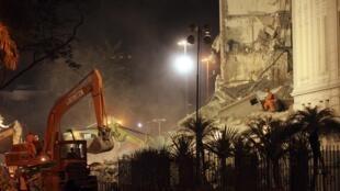 Bombeiros e tratores recolhem destroços dos prédios que desabaram no centro do Rio de Janeiro, nesta quarta-feira.