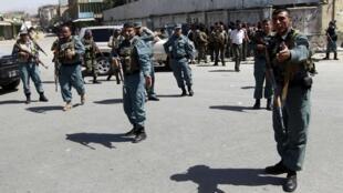Афганские полицейские на месте теракта в центре Кабула 18 июня 2011 года