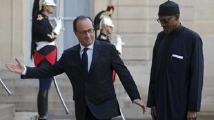 French President Francois Hollande (L) welcomes Nigeria's President Muhammadu Buhari to the Elysee Palace