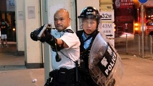 Police officer points gun towards anti-government protesters