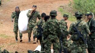 Soldados carregam corpos de colegas mortos em ataque das Farc; depois de ofensiva, Bogotá suspendeu moratória a bombardeios
