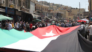 Protesters holding the Jordanian flag