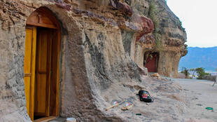La porte en bois de l'église creusée dans la roche de Warq Amba, dans la région du Tigray dans le nord de l'Ethiopie, avec en arrière-plan l'ancienne église devenue trop petite.