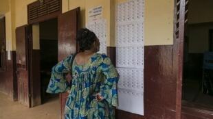 A Yaoundé, une électrice examinant les listes électorales pour y trouver son nom, lors des élections législatives et municipales, au Cameroun, le 9 février 2020.