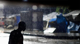 A man walks in the rain at downtown Port-au-Prince