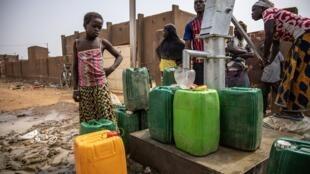 Des déplacés internes venus du nord de Burkina Faso, autour d'une pompe à eau, à Kaya, le 22 janvier 2020.