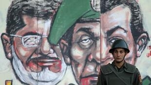 A soldier stands in front of a mural depicting Egypt's former President Mubarak (R) and President Morsi (L)