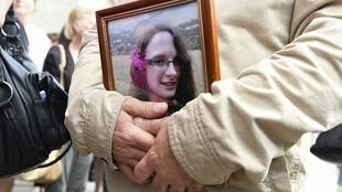 A man holds a picture of murdered French au-pair Sophie Lionnet after her funeral in Sens on 6 June, 2018.