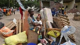Une fille et un enfant sont assis au milieu de leurs affaires après que la démolition des maisons par le gouvernement a commencé dans le quartier près de l'aéroport international d'Abidjan (Côte d'Ivoire) le 23 janvier 2020.