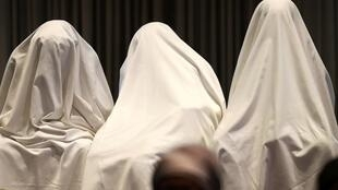 Como si fuesen fantasmas, tres alumnas de Chibok que lograron huir de Boko Haram asisten a una conferencia en Lagos, el 5 de junio de 2014.