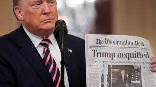Donald Trump brandit un journal faisant état de son acquittement à la Maison Blanche le 6 février 2020.
