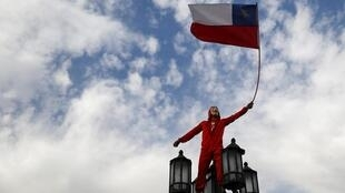 Manifestante segura a bandeira chilena durante protesto contra o modelo econômico neoliberal.