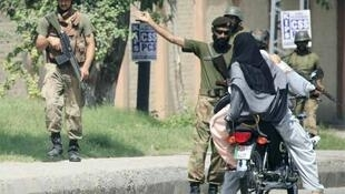 Pakistani soldiers check a man and woman on a motor bike near the Peshawar US consulate