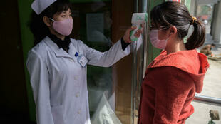 Una enfermera toma la temperatura de una joven a la entrada del Hospital del Pueblo del Distrito de Pyongchon, en Pyongyang, la capital de Corea del Norte, que asegura que no ha registrado ningún caso de coronavirus