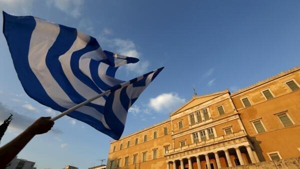 Manifestante exibe bandeira grega durante um protesto anti-austeridade em Atenas, Grécia, 29 de junho de 2015.