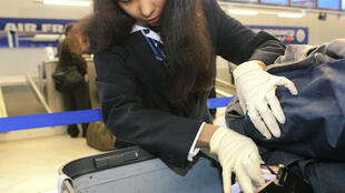 A manual security check on luggage at Paris's Charles-De-Gaulle airport