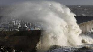A wave hits the Pornic fishing harbour in western France during this week's storms