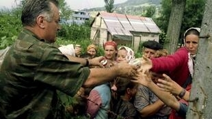 Bosnian Serb army Commander General Ratko Mladic hands out cans of beverages to Bosnian Muslims in Srebenica