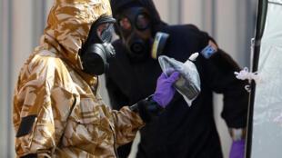 Investigadores forenses, usando roupas de proteção, saem de John Baker House, depois que foi confirmado que duas pessoas haviam sido envenenadas com o agente nervoso Novichok, em Amesbury, Inglaterra, em 6 de julho de 2018
