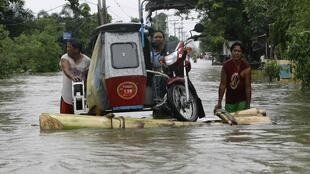 Residents wade through floodwaters brought on by typhoons
