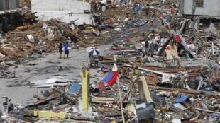 Sobreviventes caminham em meio aos destriços após passagem do supertufão Haiyan em Tacloban no centro das Filipinas.