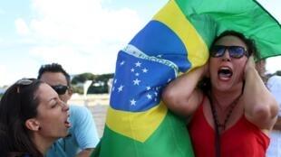 Manifestante antigoverno (esquerda) e pró-governo durante um protesto contra a nomeação do ex-presidente Lula, em frente ao Palácio do Planalto em Brasília.