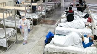 Equipes médicas trabalham com roupas de proteção ao atender pacientes em hospital chinês.