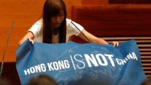 """游蕙禎在立法會展示""""香港不是中國""""(Hong Kong is not China)的藍色旗幟,2016年10月12日。"""