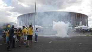 Torcedores se afastam de uma nuvem de gás lacrimogênio, utilizado pela polícia para dispersar os manifestantes que protestavam ao redor do estádio Mané Garrinche, em Brasília, neste sábado, 15 de junho de 2013.