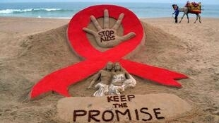 A man walks a camel past a sand sculpture created by Indian sand artist Sudarshan Patnaik to create awareness about AIDS ahead of World AIDS Day