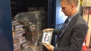 """Представитель бельгийской полиции держит в руках брикет с кокаином, маркированный логотипом """"Единой России"""". Кадр из видео бельгийской телерадиокомпании VRT"""