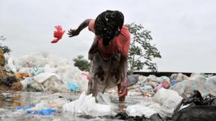 Une femme nettoie des sacs en plastique, en banlieue d'Abidjan.
