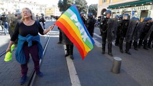 Активистка-антиглобалистка Женевьев Леге на акции «желтых жилетов» в Ницце, 23 марта. Она вышла с радужным флагом с надписью «мир». При разгоне демонстрации она упала и получила черепно-мозговые травмы