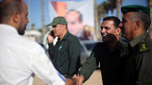 Representante da segurança palestina é cumprimentado na fronteira de Rafah com o Egito.