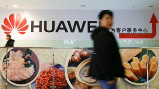 A man walks past a Huawei sign in a mall in Beijing, China