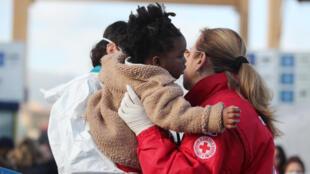 Une volontaire de la Croix-Rouge aide un enfant à l'arrivée d'un bateau de migrants à Palerme, en Italie, le 18 janvier 2018.