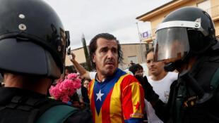 Um militante pela independência da Catalunha enfrenta policiais espanhóis em Sant Julià de Ramis, neste 1° de outubro de 2017.