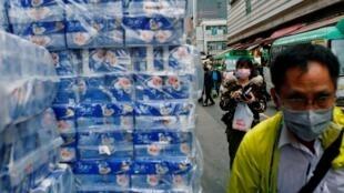 Des gens portant des masques passent à côté d'un stock de rouleaux de papier hygiénique à Hong Kong, Chine, le 8 février 2020. Depuis la ruée sur ce produit de base fait craindre une pénurie.