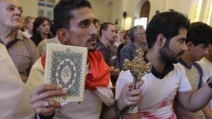 Um iraquiano rezando, com um Corão e um crucifixo, em uma igreja de Bagdá. 20 de julho de 2014.