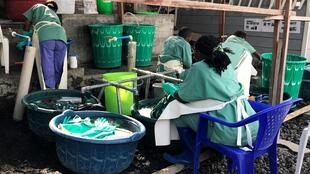 Health workers clean their clothes at an Ebola centre in Goma, 18 July 2019
