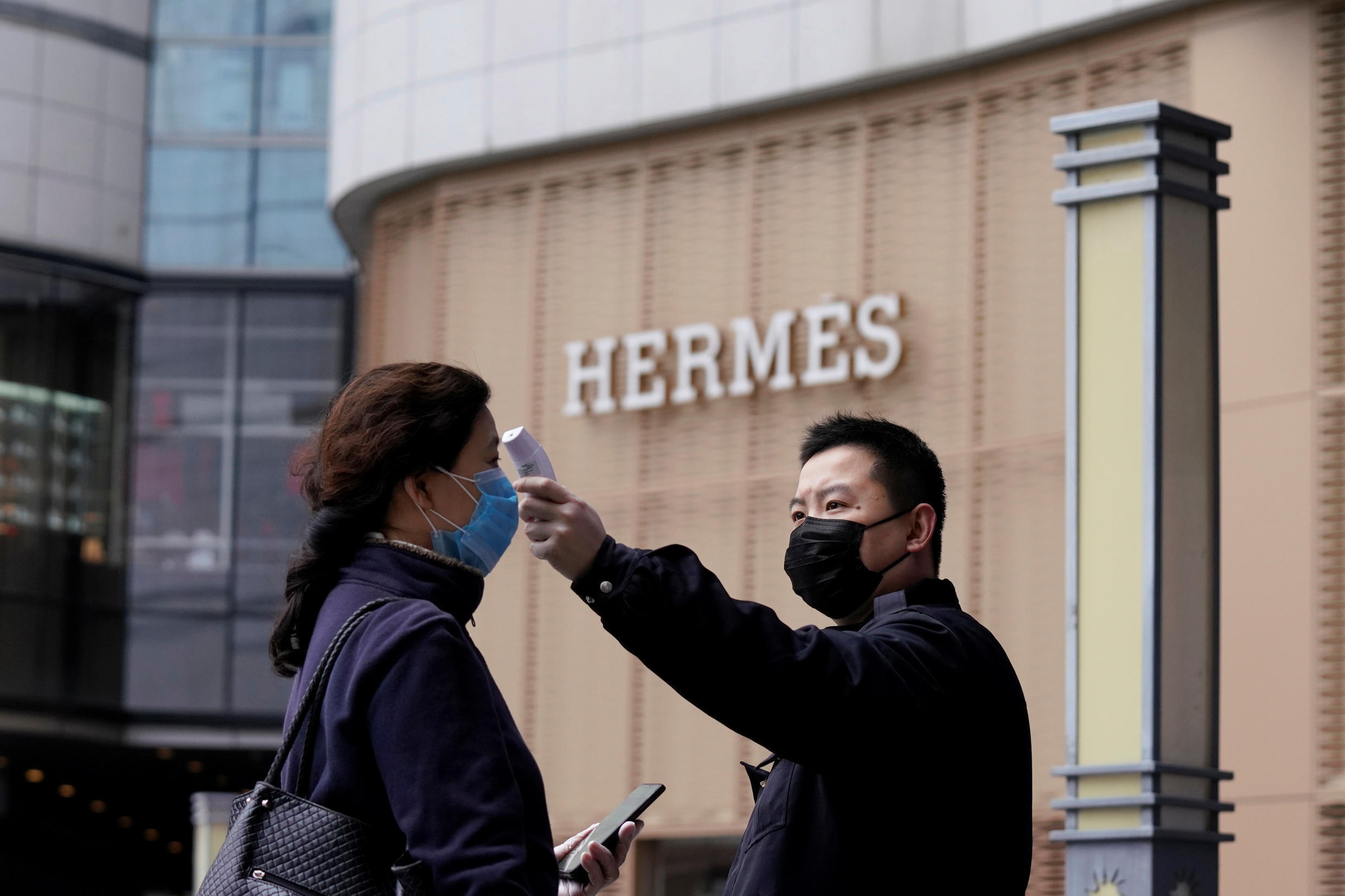 A management staff measures the body temperature of a woman entering a shopping mall near a Hermes store in Wuhan, Hubei province, the epicentre of China's coronavirus disease (COVID-19) outbreak, March 30, 2020.