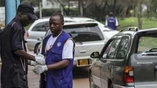 Security personnel wear gloves to check motorists entering and exiting Mulago hospital in Uganda's capital of Kampala