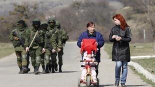 Mulheres andam com carrinho de bebê com milicianos armados ao fundo, na Crimeia