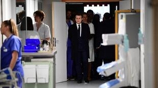 French President Emmanuel Macron (C) visits the Pitie-Salpetriere hospital in Paris on February 27, 2020 where the first French victim of COVID-19 passed away the day before.